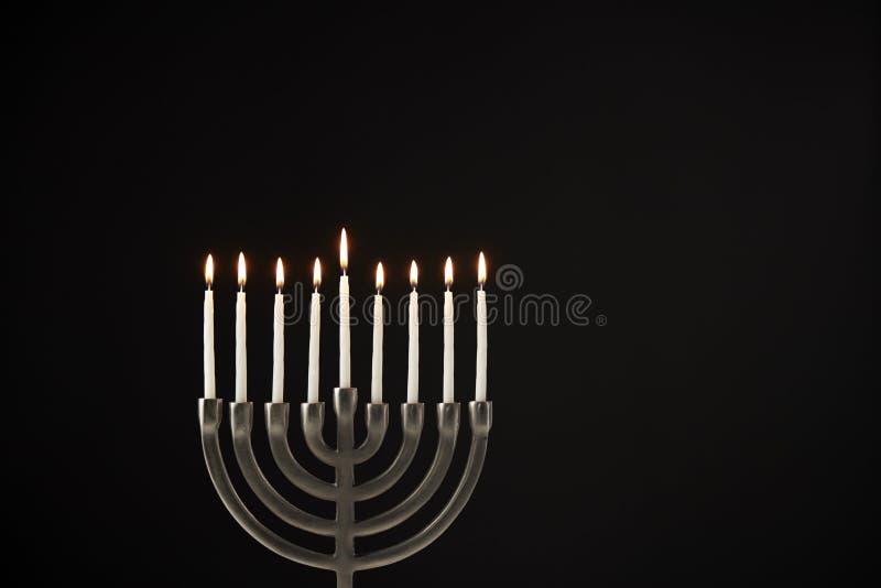 Zaświecać świeczki Na metalu Hanukkah Menorah Przeciw Czarnemu Pracownianemu tłu obraz stock