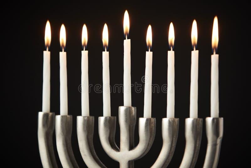 Zaświecać świeczki Na metalu Hanukkah Menorah Przeciw Czarnemu Pracownianemu tłu obrazy stock