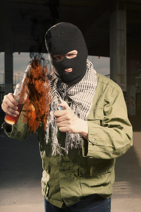 Zaświecać flammable butelka w zamaskowanych mężczyzna rękach obrazy royalty free
