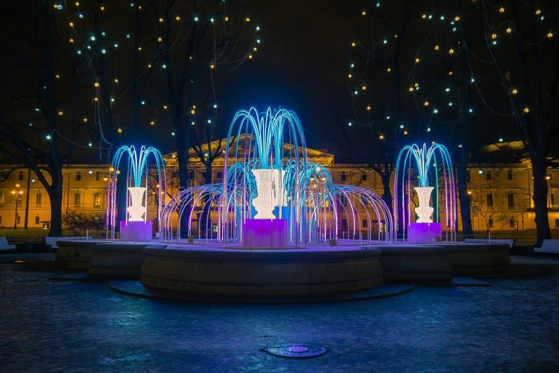 Zaświecająca fontanna blisko zima pałac w nocy iluminaci zdjęcia stock