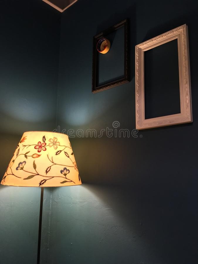 Zaświecająca kwiat lampa w ciemnym pokoju z abstrakt pustymi ramami na ścianie i ashtray w jeden one fotografia royalty free
