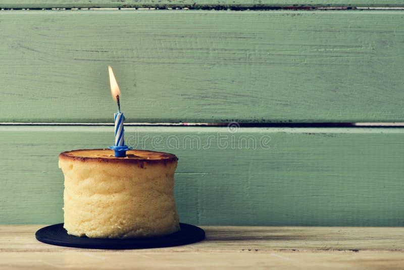 Zaświecająca urodzinowa świeczka na cheesecake zdjęcia stock