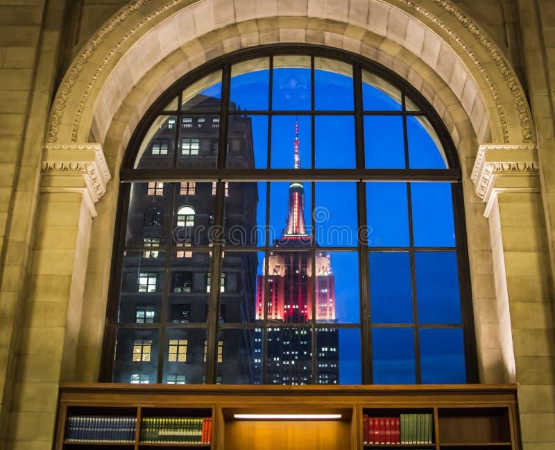 Zaświecający empire state building jak przeglądać przez okno Nowy Jork biblioteki publicznej Czytelniczy pokój na zimy popołudniu zdjęcie royalty free