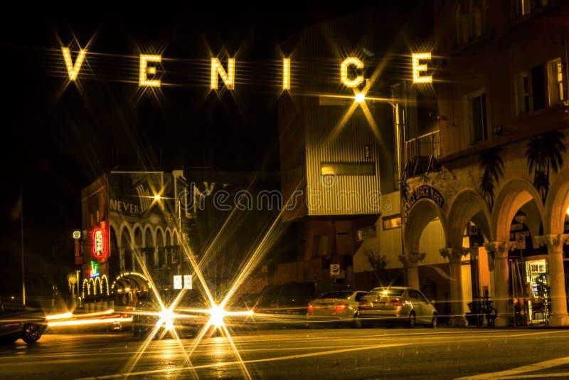 Zaświecający znak uliczny nad samochodu starburst światłami zaznacza wejście Venice Beach, Kalifornia zdjęcie royalty free