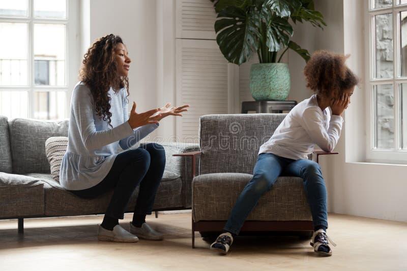 Zażarty afrykański dzieciak ignoruje mamy łajanie, rodzic i dziecko, kantujemy obraz royalty free