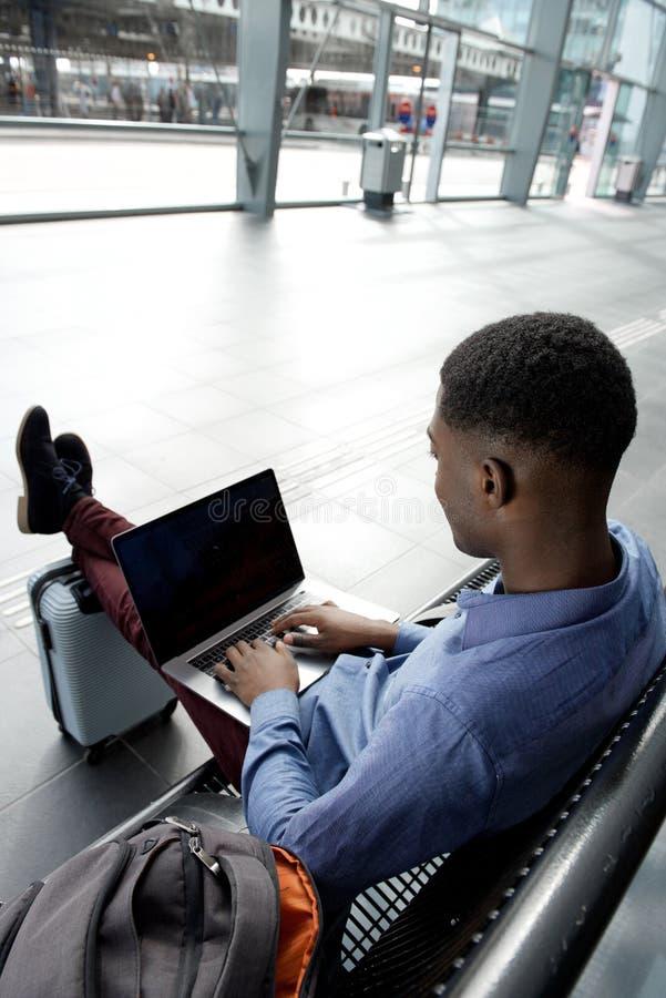 Za amerykanin afrykańskiego pochodzenia biznesmena podróżnym czekaniem na ławce z torbami i laptopem zdjęcie stock