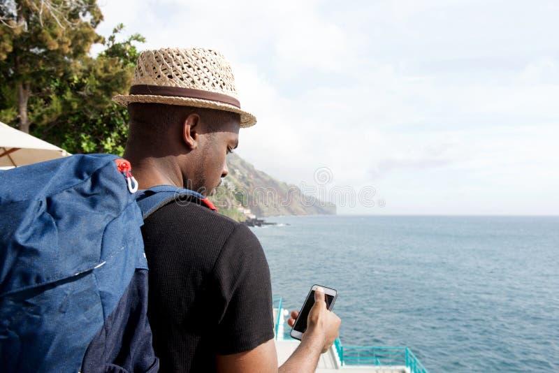 Za amerykanin afrykańskiego pochodzenia podróży mężczyzną patrzeje telefon komórkowego morzem z torbą zdjęcia royalty free