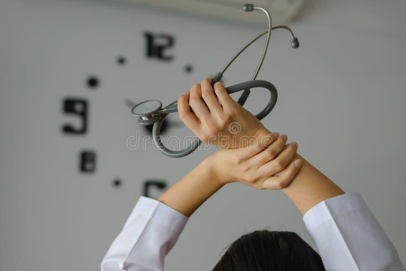 Za młodą kobiety lekarki mienia stetoskopu pozycją i ręką up dla relaksować po tym jak koniec praca z zegarem na ścianie zdjęcie stock