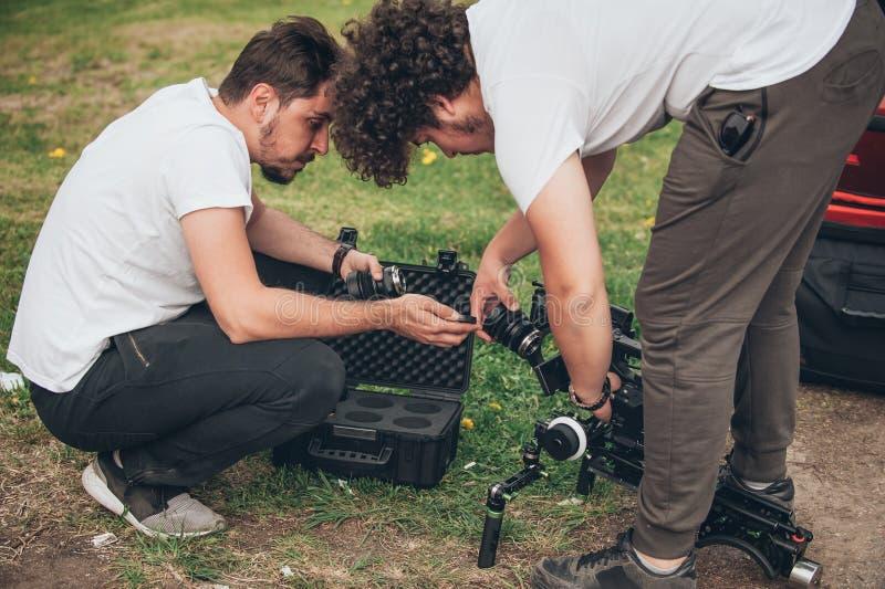 za sceną Kamerzysty i asystenta zmian obiektyw na kamerze fotografia stock