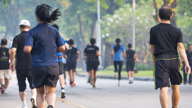 Za widokiem plecy ludzie bieg przy drzewo ogródem obrazy stock