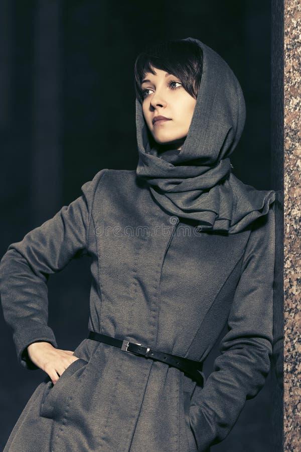 Zaafde jonge modevrouw met een klassieke jas en hoofddoek stock foto's