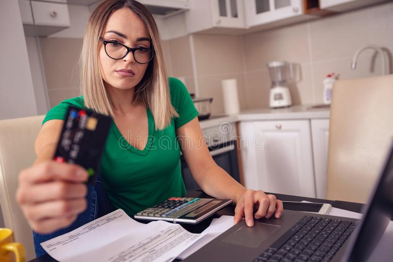 Zaakcentowana biznesowa kobieta pracuje w domu - płacący wystawia rachunek e bankowość obraz royalty free