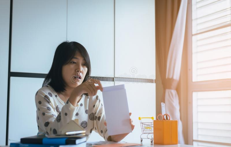 Zaakcentowana kobieta otwiera kopertowego dyrekcyjnego dług, elektryczność i wodnego rachunek, fotografia stock
