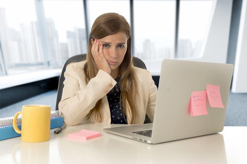 Zaakcentowana kobieta pracuje z laptopem na biurku w zapracowanym zdjęcie stock