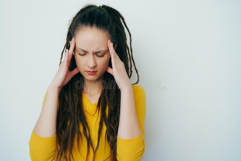 Zaakcentowana sfrustowana Piękna dziewczyna z dreadlocks w żółtym jaskrawym pulowerze i tensely myśleć, trzymający rękę przy świą zdjęcia stock