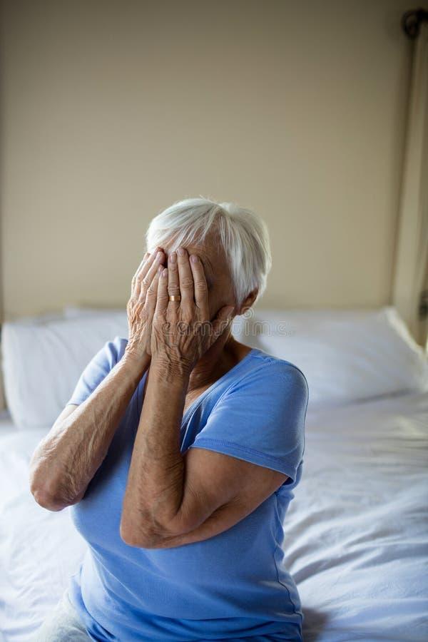 Zaakcentowana starsza kobieta zakrywa jej twarz z rękami fotografia stock