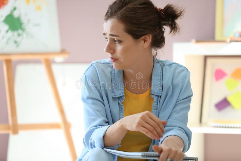 Zaakcentowany żeński malarz pracuje w studiu obrazy stock