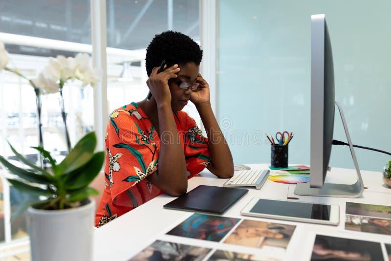 Zaakcentowany żeński projektant grafik komputerowych obsiadanie przy biurkiem zdjęcia stock