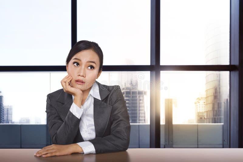 Zaakcentowany azjatykci bizneswoman myśleć rozwiązanie podczas gdy pracujący obraz royalty free
