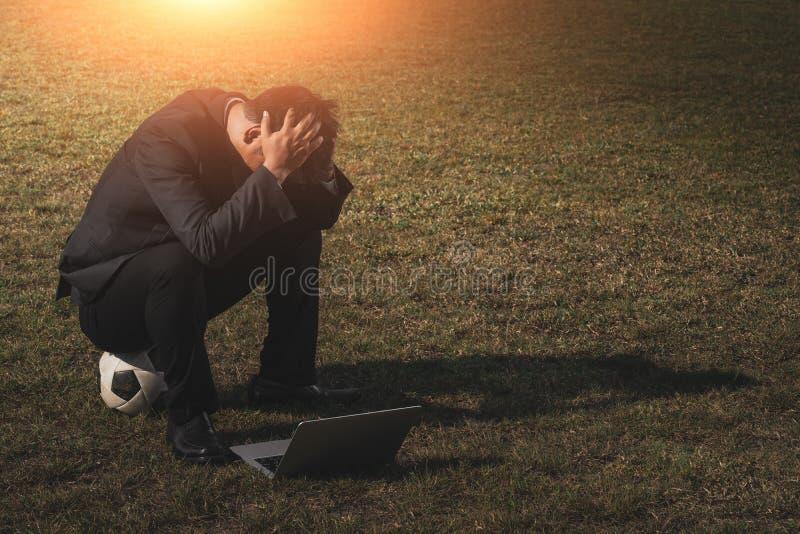 Zaakcentowany biznesmen z głową w rękach przy boisko do piłki nożnej, Zaakcentowany młody biznesmena obsiadanie na zewnątrz korpo obraz stock