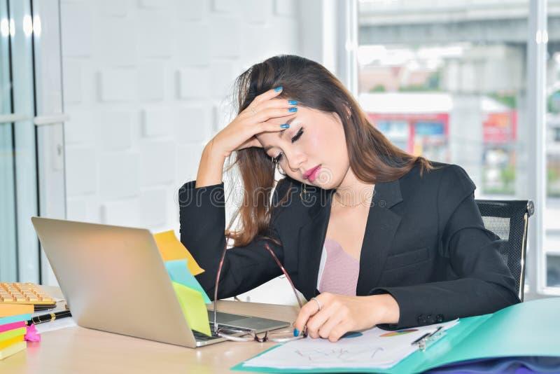 Zaakcentowany biznesowej kobiety obsiadanie i mienie przewodzimy przez bólowej migreny w nowożytnym biurze fotografia royalty free