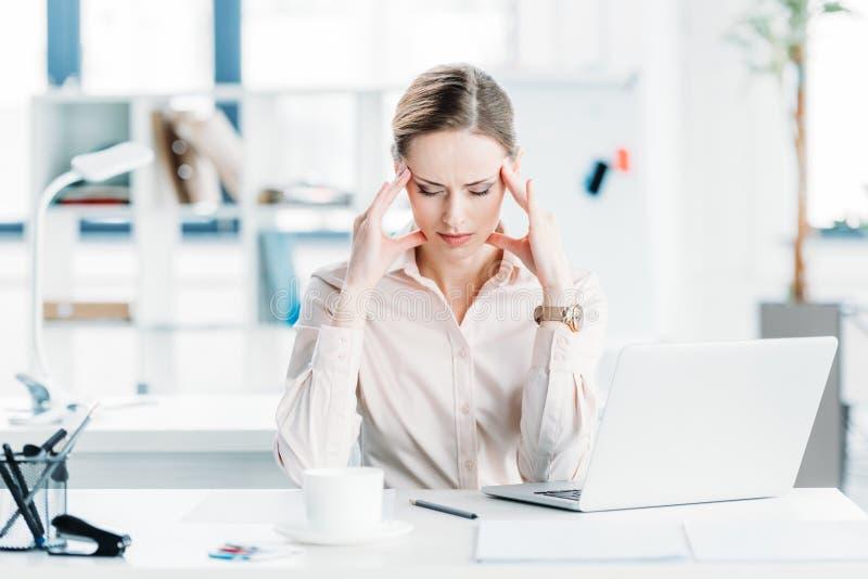 Zaakcentowany bizneswomanu obsiadanie przy miejscem pracy w nowożytnym biurze obraz stock