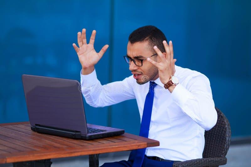 Zaakcentowany gniewny młody biznesowy mężczyzna z laptopu obsiadaniem przy stołem obraz royalty free
