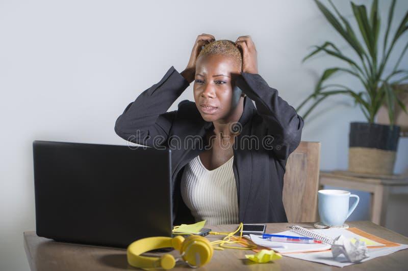Zaakcentowany i sfrustowany afro Amerykański murzynki działanie przytłaczał przy biurowy laptopu biurka gestykulować smutnym i d  fotografia royalty free