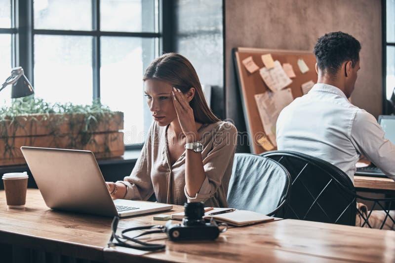Zaakcentowany i zmęczony Sfrustowana młoda kobieta używa komputer podczas gdy obrazy royalty free
