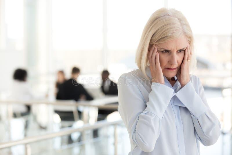 Zaakcentowany męczący dojrzały bizneswoman cierpi od migreny w o zdjęcia stock
