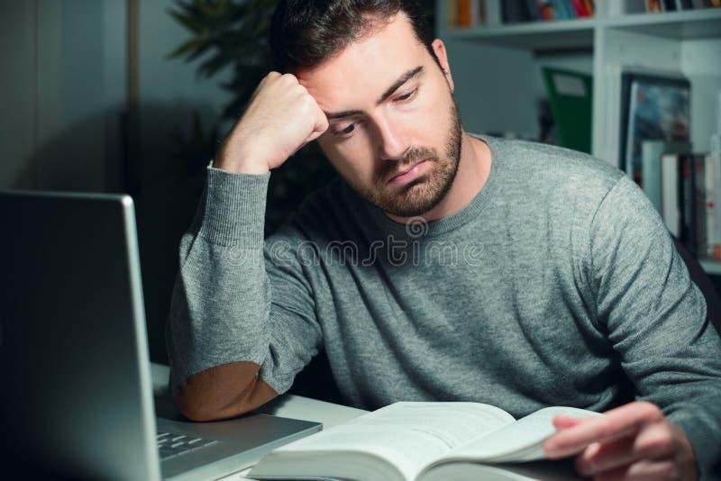 Zaakcentowany męski uczeń studiuje póżno przy nocą obrazy stock