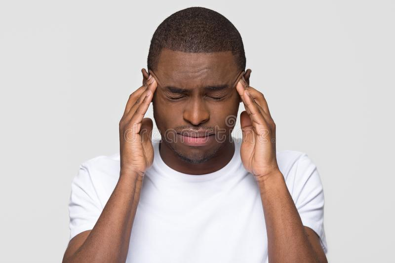 Zaakcentowany młody amerykanin afrykańskiego pochodzenia mężczyzny uczucia ból ma okropną migrenę zdjęcia royalty free