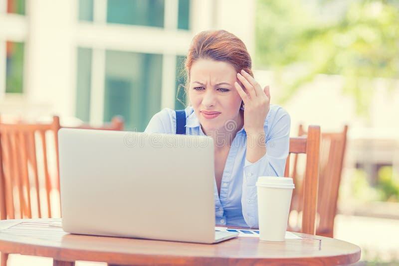 Zaakcentowany nierad zmartwiony biznesowej kobiety obsiadanie przed laptopem zdjęcia royalty free