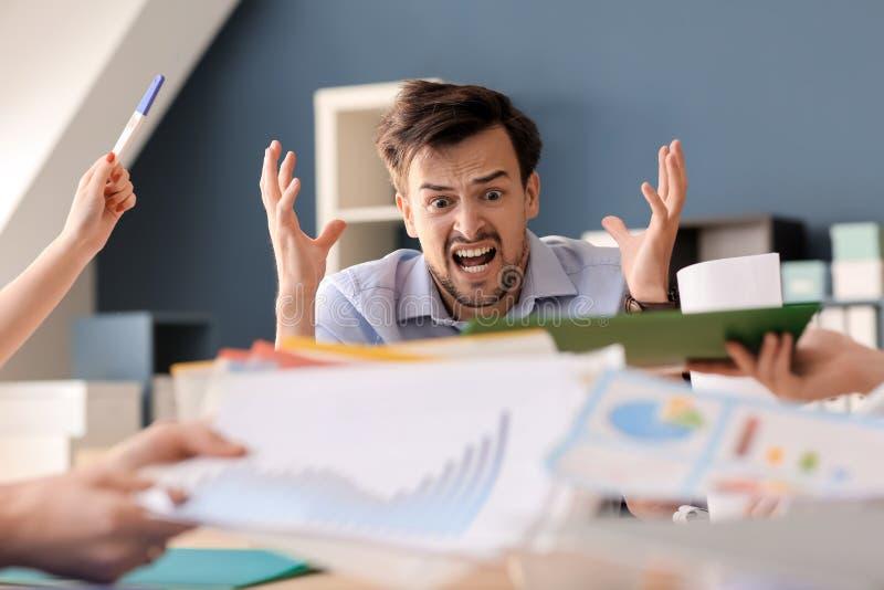 Zaakcentowany pracownika obsiadanie przy stołem w biurze zdjęcie stock