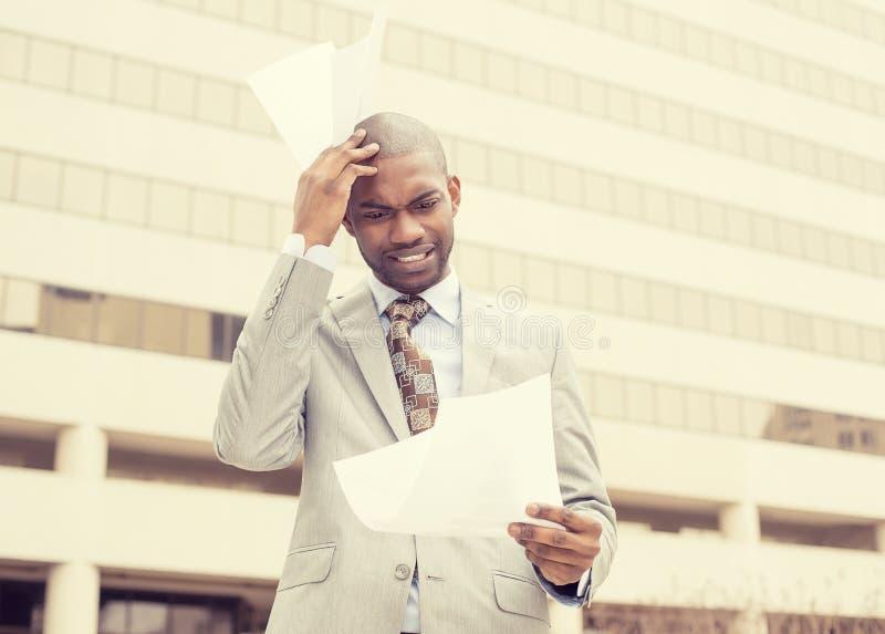 Zaakcentowany sfrustowany mężczyzna trzyma patrzeć dokumenty obrazy royalty free