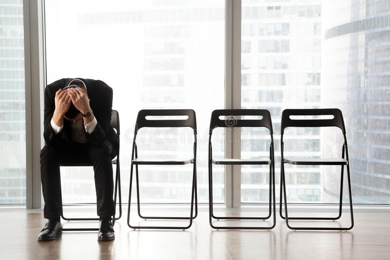 Zaakcentowany wzburzony biznesmena obsiadanie na krześle, otrzymywająca zła wiadomość zdjęcie royalty free