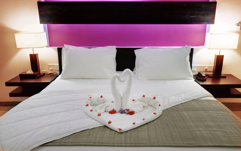 Zaal in een hotel met zwanen van de handdoek op het jonggehuwdenbed stock afbeeldingen