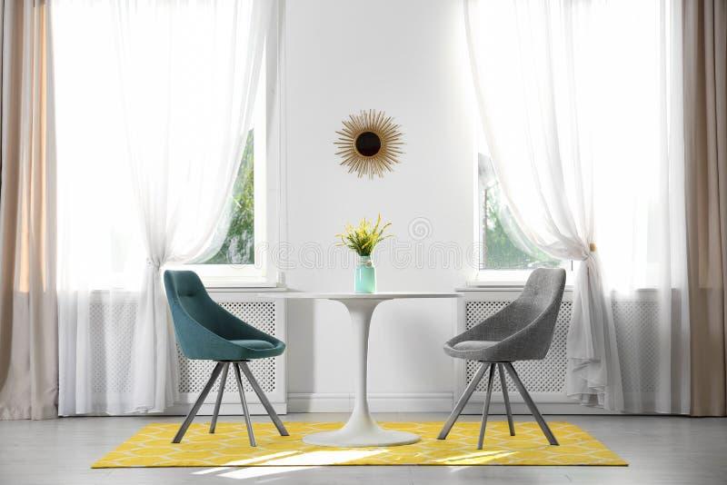 Zaal met comfortabele lijst, stoelen en modieus decor stock foto