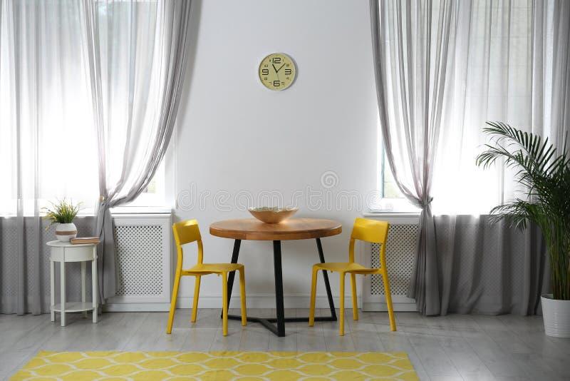 Zaal met comfortabele lijst, stoelen en modieus decor royalty-vrije stock fotografie
