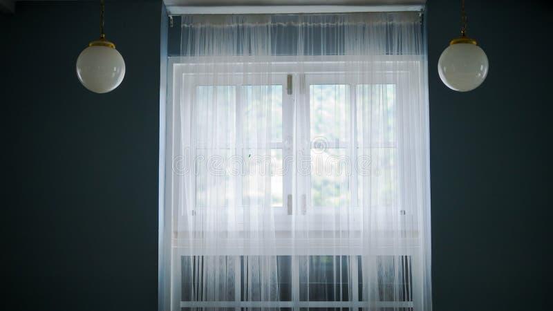 Zaal met donkere muur binnenlandse witte gordijnen op venster stock afbeelding