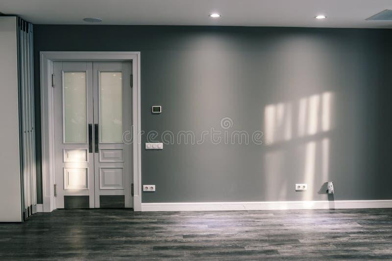 Zaal met een grijze muur en een witte deur Glasdeur met het scherpen Op de vloer en muurzonglans Harmonische kleuren ontwerper stock foto's