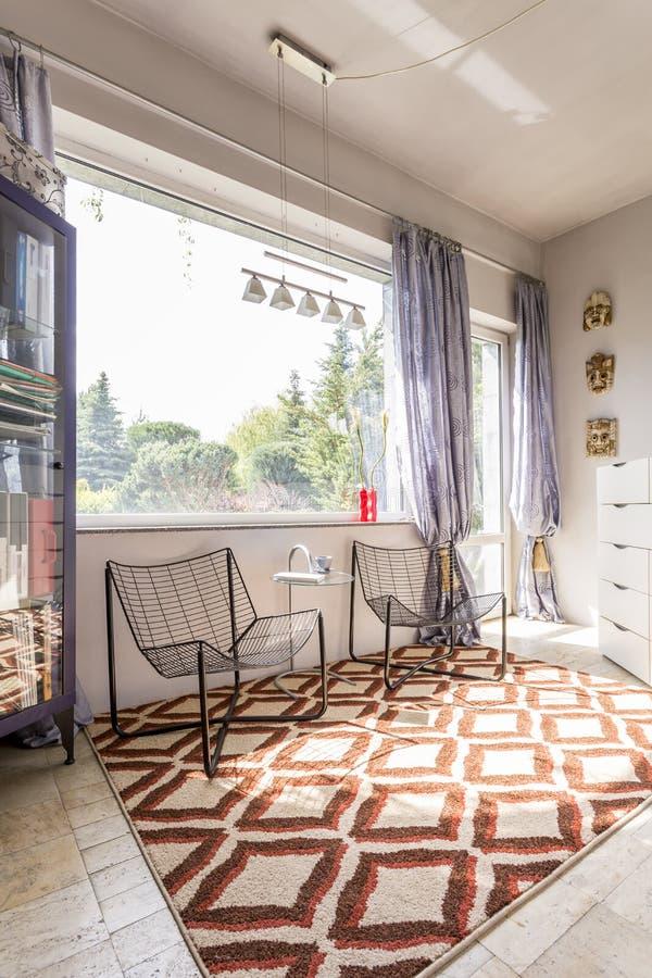 Zaal met minimalistic stoelen en etnisch tapijt royalty-vrije stock foto