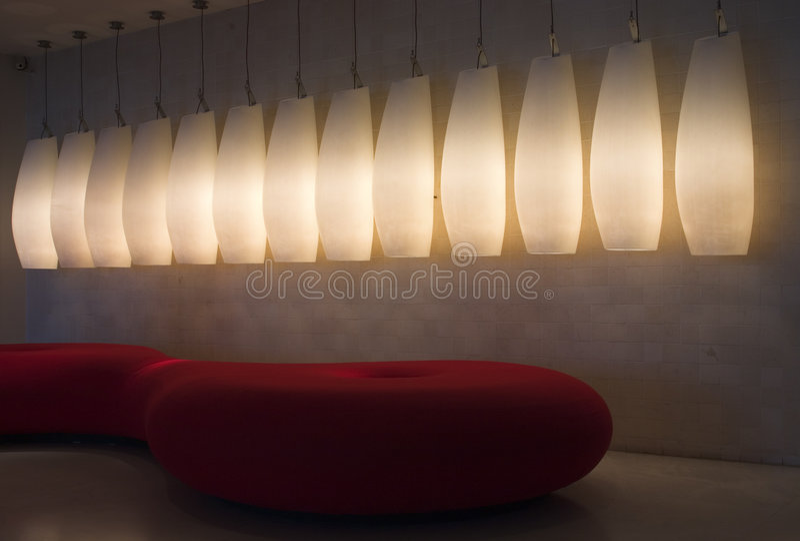 Zaal met rode bank en lampen stock foto