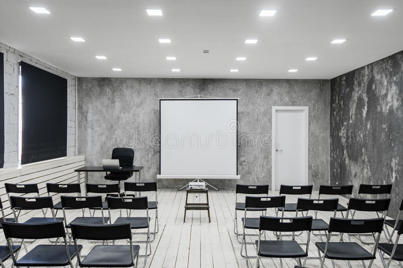 Zaal voor lezing met heel wat donkere stoelen De muren zijn wit, zolderbinnenland Op het recht is er een deur op stock foto