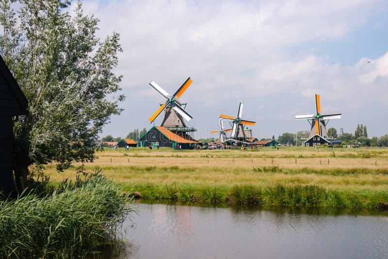 Zaanse Schans, Netherlands - 06/14/2019: Old dutch windmills in historical village. Wooden windmills in field with river. royalty free stock photo