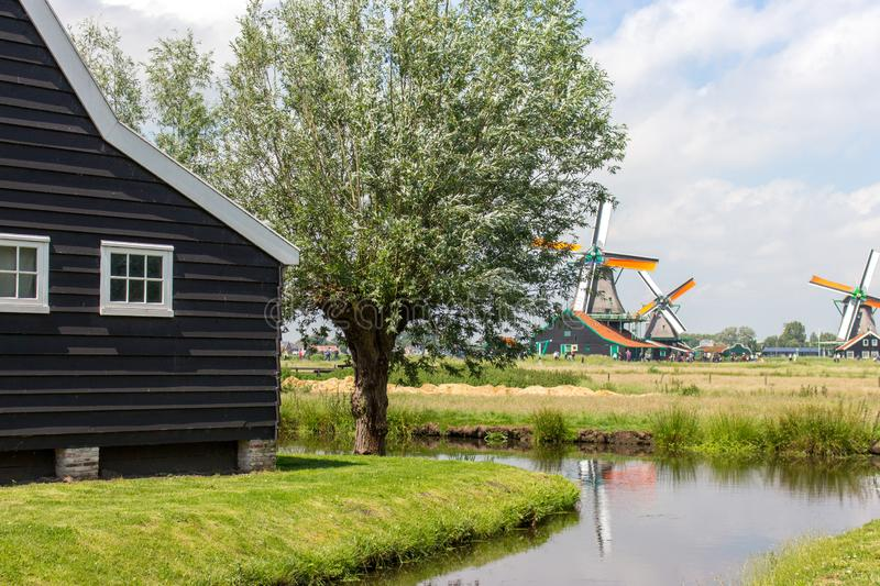 Old dutch windmills, pond and wooden house in historical village. Holland mills in field with river and ancient building. Zaanse Schans, Netherlands - 06/14/ stock photography