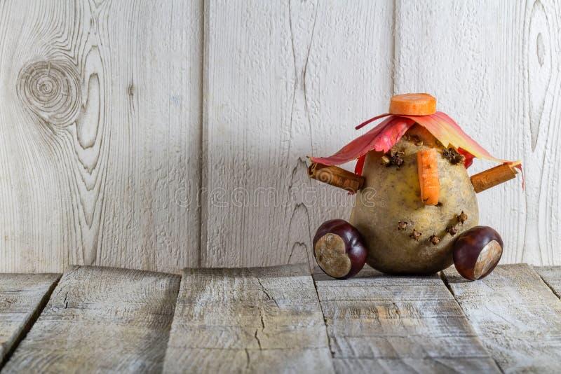 Zabawa kartoflany charakter z cisawymi jesień liśćmi na białym backgr zdjęcie stock