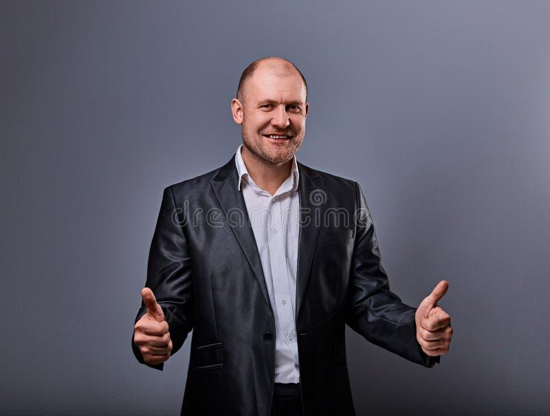 Zabawa komiczny łysy biznesowy mężczyzna w czarnym kostiumu pokazuje palcowego sukcesu kciuk w górę znaka na popielatym tle zbliż zdjęcia royalty free