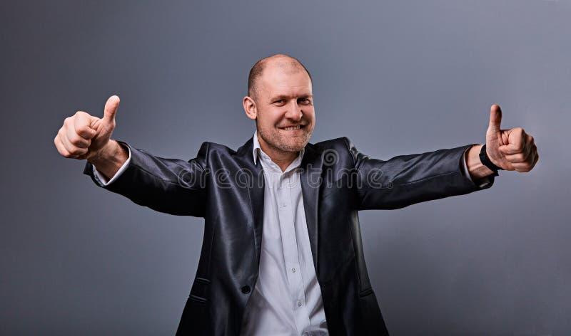 Zabawa komiczny łysy biznesowy mężczyzna w czarnym kostiumu pokazuje palcowego sukcesu kciuk w górę znaka na popielatym tle zbliż obrazy stock
