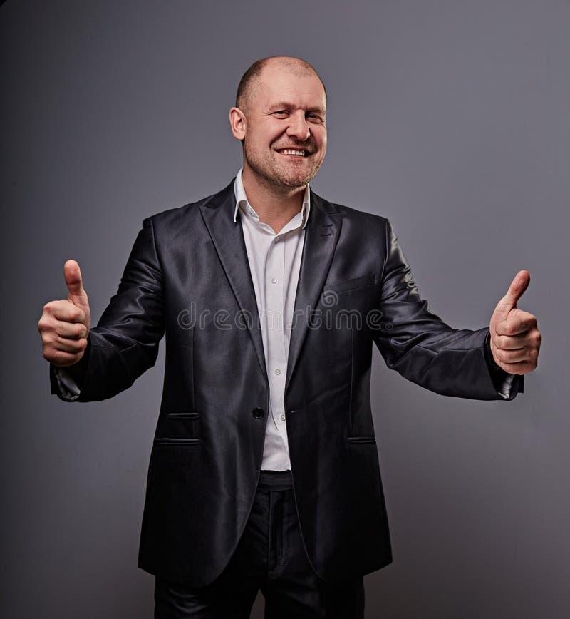 Zabawa komiczny łysy biznesowy mężczyzna w czarnym kostiumu pokazuje palcowego sukcesu kciuk w górę znaka na popielatym tle zbliż zdjęcia stock